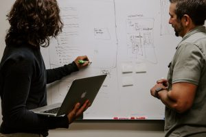 ホワイトボードで会議をする社員たちのイメージ画像